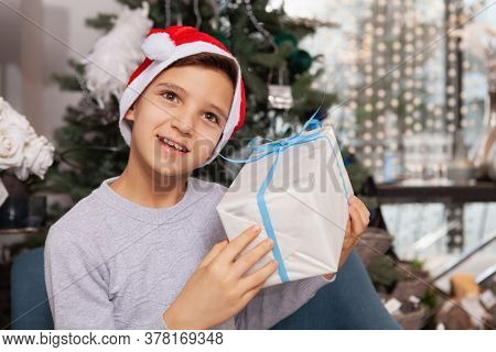 Adorable Young Boy In Santa Claus Hat Listening To A Present In His Hands. Cheerful Little Boy With