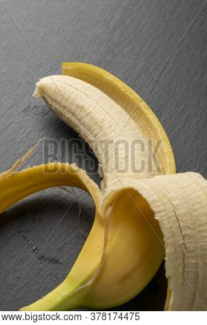 Peeled Ripe Banana With A Bright Yellow Skin On A Dark Gray Textured Background. Tropical Ingredient