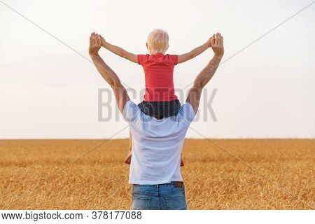 Son Sitting On Father's Shoulders With My Hands Up. Happy Childhood And Fatherhood.