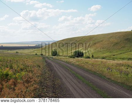 Highway Going Through Rural Pastoral Landscape. Wheat Field With Haystacks. Harvesting. Hills And Fo