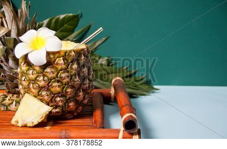 Exotic Tropical Cocktail Drink In A Pineapple With Plumeria Frangipani Flower And Palm Leaf For Deco