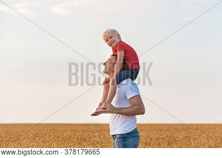 Happy Boy Sitting On Shoulders Of Young Father. Dad And Son In Countryside.