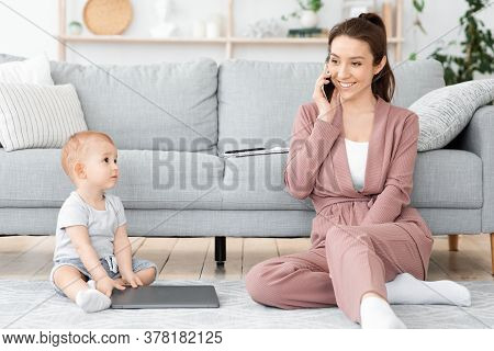 Careless Mom. Young Mother Talking On Cellphone At Home And Ignoring Her Baby Son, Free Space