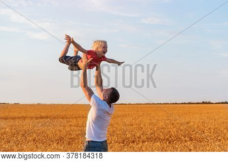 Son Flies With Father. Dad Throws Up Child. Daddy Playing With Son Outdoors.