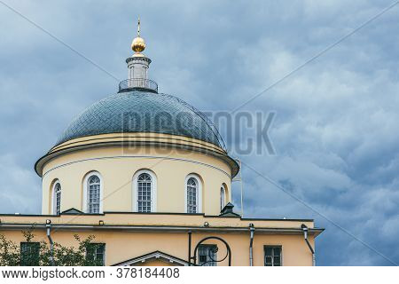 A Green Dome With Elongated Arched Windows Topped With A Golden Dome Against A Stormy Sky. Capital O