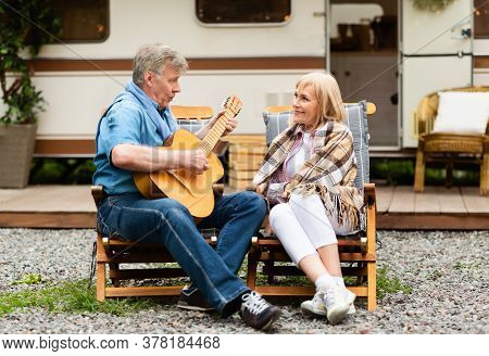 Romantic Senior Man Playing Guitar And Singing Song To His Wife Near Motorhome At Campground