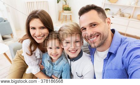 Cute Family Selfie. Happy Parents And Children Smiling Posing To Camera Sitting On Couch At Home.