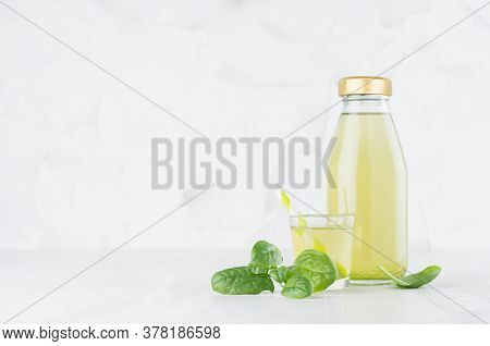 Fresh Vegetable Green Spinach Juice In Glass Bottle Mock Up With Glass, Straw, Leaves In Soft Light