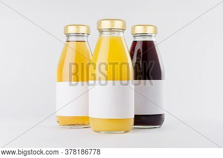 Yellow, Red Fruit And Berries Juices Collection In Glass Bottles With Cap, White Blank Labels, Group