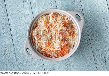 White Ceramic Pan Full Of Grated Cabbage And Carrot On Wooden Blue Table Surface Made Of Planks. Coo