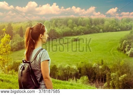 Beautiful Meadow And Hill Landscape With Tourist Girl. Portrait Of Woman With Backpack Standing On T