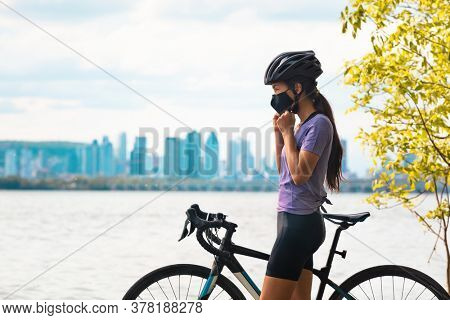Wearing covid-19 mask while riding bike. Sport cyclist woman biking putting on face mask for Covid-19 prevention during summer outdoor leisure exercise activity. Fitness outside.