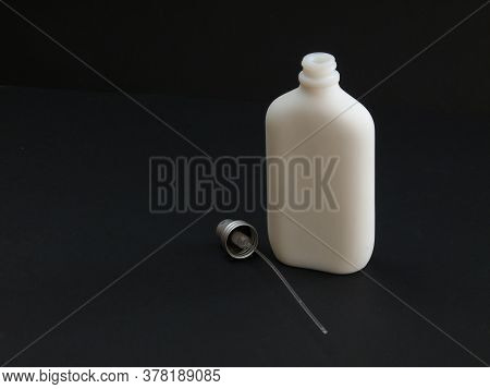 Open White Non-transparent Bottle With Perfume Next To The Dispenser On A Black Background