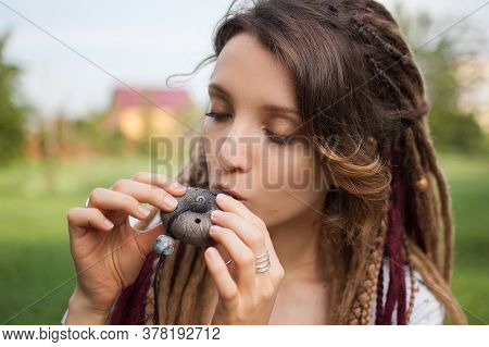 Close-up Outdoors Portrait Of Young Female Shaman With Long Dreadlocks Playing On Traditional Hutsul
