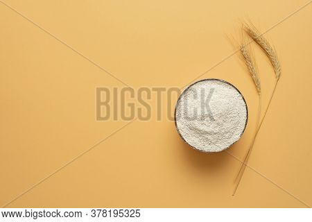 Bowl Of Wholemeal Flour Isolated On A Beige Background. Top View With A Bowl Of Wholemeal Flour And