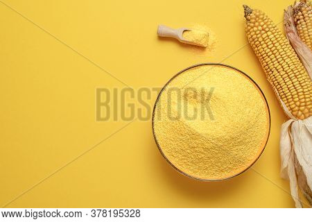 Bowl Of Cornflour Above View Isolated On A Yellow-colored Background. Polenta In A Bowl And Dry Corn