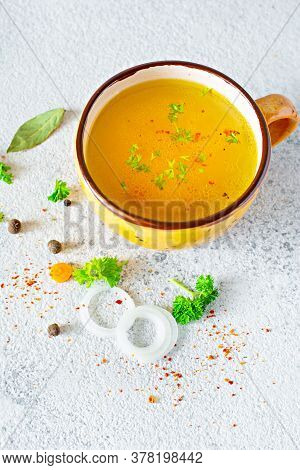 Homemade Chicken (bone) Broth/bouillon With Vegetables, Spices And Herbs In A Bowl (cup) On A Light