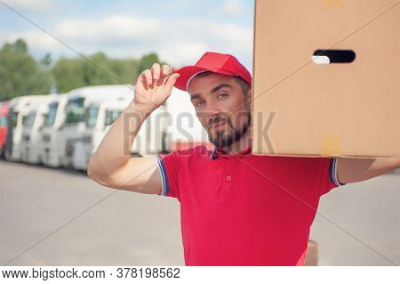 A Man In A Red Suit In His Hands With A Cardboard Box Against The Background Of The Van. Concept On