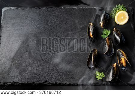 Black mussel with lemon serve on black stone plate. Fresh seafood food and european cuisine gourmet concept.