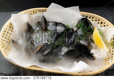 Fresh black mussel seafoon in basket with lemon. Fresh food and market concept.