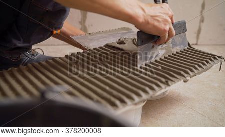 A Worker Applies Glue To The Tiles. Worker Applies Adhesive To Tiles On The Wall. Installation Of Ti