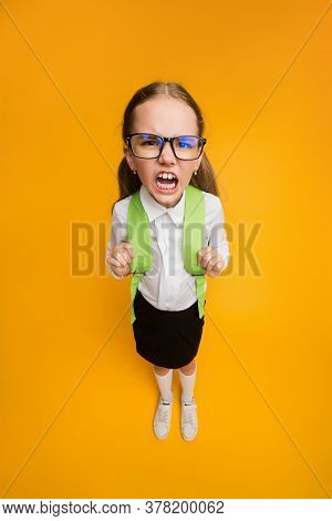 Discontented Schoolgirl In Eyeglasses Frowning Looking At Camera Standing On Yellow Studio Backgroun