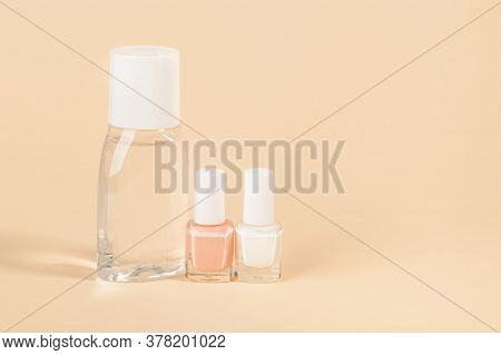 Bottle With Nail Varnish Remover, White And Pale Pink Nail Polish On A Powdery Color Background. Man