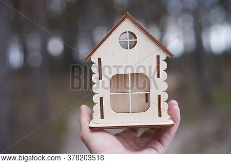 Miniature Wooden House In Male Hand Outdoor Nature. Real Estate Concept. Modern Housing. Eco-friendl