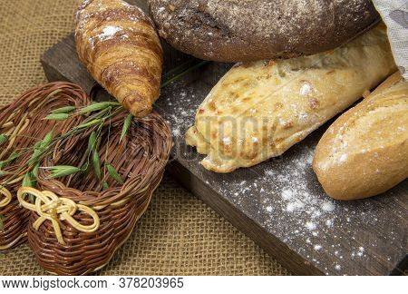 Several Types Of Bread Lie On A Rough Wooden Board Against The Background Of Matting.