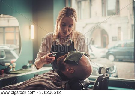 Young Specialist Carefully Cuts the Beard of a Man.