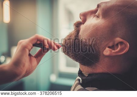 Handsome Client Close His Eyes While Barber Woman Combs His Beard.