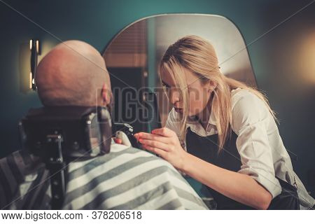Young Concentrated Blond Woman Does Beard Cut to a Bald Client.