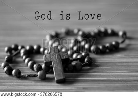 Christian Inspirational Quote - God Is Love. On Black And White Background Of Wooden Rosary Beads Wi