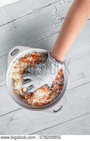 Hand Of Teenager In White Glove Squeezing Grated Cabbage And Carrot In Pan On Wooden White Table. Co