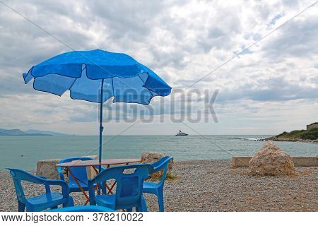 Blue Umbrella, Table And Chairs At The Deserted Sea Beach On A Cool Windy Summer Day
