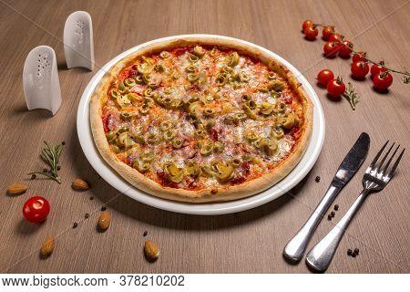 Capricciosa Pizza Thin Cake, Tomato Sauce, Ham, Olives, Marinated Mushrooms Mozzarella Basil.