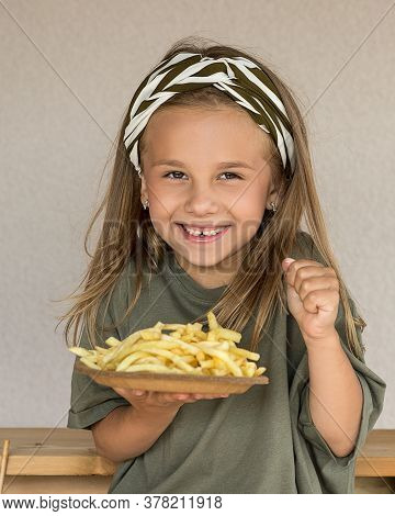 Photo Of A Small Happy Beautiful Girl 6 Years Old Holds A Plate Of French Fries. Children's Favorite