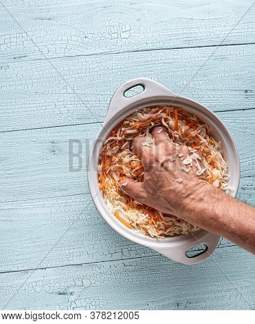 Hand Of Man Squeezing Grated Cabbage And Carrot In Ceramic Pan On Wooden White Table. Cooking Stage
