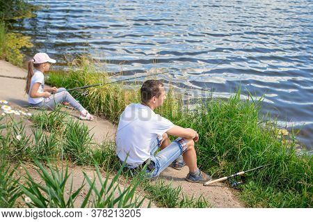 Father With Daughter Sit On The Shore Of Lake With Fishing Rods And Catch Fishconcept Of Outdoor Hol