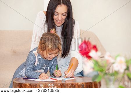 mother with daughter drawing on the table isolation during a pandemic