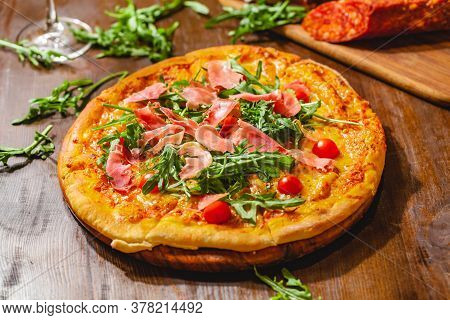 Italian Pizza With Prosciutto (parma Ham), Arugula (salad Rocket) And Cherry Tomatoes On Wooden Boar