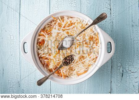 Pan Full Of Grated Cabbage And Carrot On Wooden Blue Table. Salt And Pepper In Two Metal Spoons Are