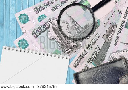 1000 Russian Rubles Bills And Magnifying Glass With Black Purse And Notepad. Concept Of Counterfeit
