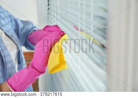 Woman Cleaning Window Blinds With Rag Indoors, Closeup