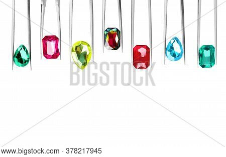 Set Of Tweezers With Different Shiny Gemstones On White Background