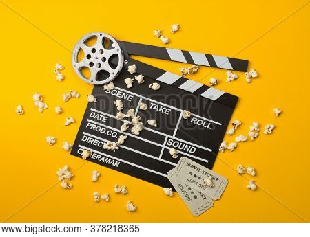 Single, Black, Open Movie Clapper Or Clapper-board With Film Reel, Popcorn And Movie Theatre Tickets