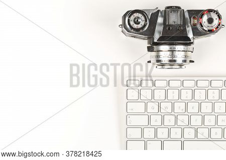 Retro Analog Slr Camera Next To Computer Keyboard On White Background, Digital Photography Or Image