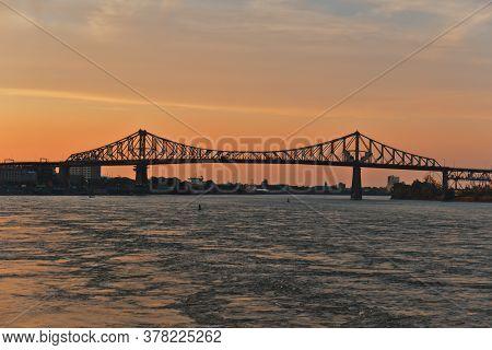A Skyline View A Steel Bridge Across A River At Sunset. Jacques Cartier Bridge Across Saint Laurent