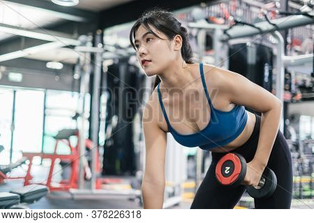 Sporty Young Asian Women Workout Exercise Dumbbell Row Pulling With Dumbbell In The Fitness Gym, Spo