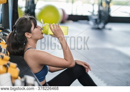 Sporty Young Asian Woman After Successful Workout In Fitness Gym Holding Bottle Of Protein Shake And